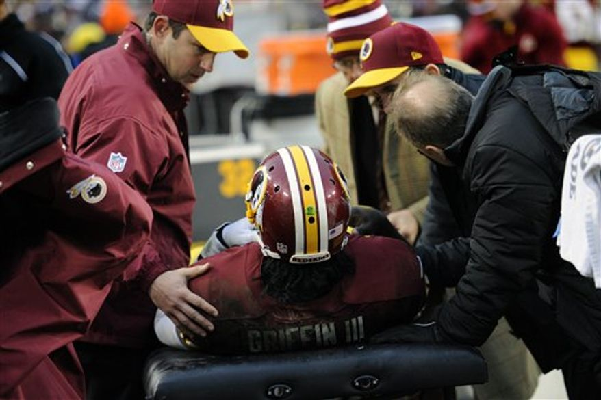 Washington Redskins quarterback Robert Griffin III is worked on by trainers after a knee injury during the second half of an NFL football game against the Baltimore Ravens in Landover, Md., Sunday, Dec. 9, 2012. (AP Photo/Nick Wass)