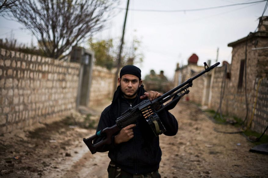 **FILE** A Free Syrian Army fighter poses Dec. 12, 2012, as he carries his weapon in the northern province of Aleppo, Syria. Syria's civil war has killed more than 40,000 people. (Associated Press)
