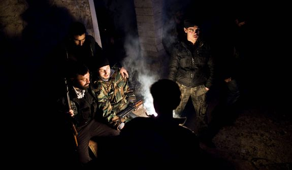 Free Syrian Army fighters warm themselves Dec. 12, 2012, in the northern province of Aleppo, Syria. Syria's civil war has killed more than 40,000 people. (Associated Press)