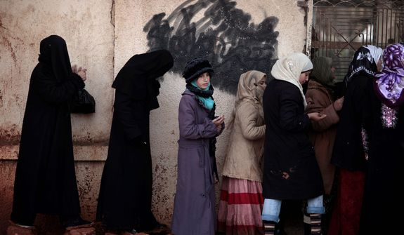 Syrian women wait outside a bakery shop to buy bread in Maaret Misreen, near Idlib, Syria, on Dec. 12, 2012. (Associated Press)