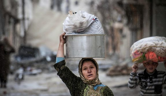 A Syrian woman and girl carry their belongings Dec. 11, 2012, after their home was damaged due to fighting between Free Syrian Army fighters and government forces in Aleppo, Syria. (Associated Press)