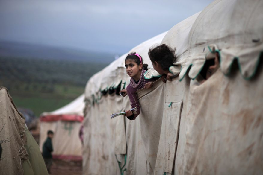 Syrian girls who fled their homes with their families peek out of their makeshift school at a camp for displaced Syrians in the village of Atmeh, Syria, on Dec. 10, 2012. (Associated Press)
