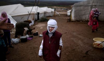 Abdullah Ahmed, 10, who suffered burns in a Syrian government airstrike and fled his home with his family, stands outside their tent at a camp for displaced Syrians in the village of Atmeh, Syria, on Dec. 11, 2012. This tent camp sheltering some of the hundreds of thousands of Syrians uprooted by the country's brutal civil war has lost the race against winter: the ground under white tents is soaked in mud, rain water seeps into thin mattresses and volunteer doctors routinely run out of medicine for coughing, runny-nosed children. (Associated Press)