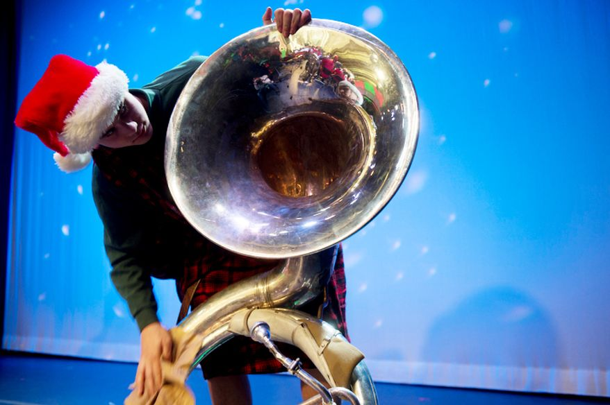 Gunnar Tokar, 15, of Damascus, Md. polishes his tuba before the start of the rehearsal for Tuba Christmas 2012 at the Millennium Stage at the Kennedy Center. They rehearsed for two hours before performing on the Millennium Stage at 6 p.m. (Barbara L. Salisbury/The Washington Times)