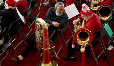 Thomas Smith, left, of Washington, D.C. and Rod Ellis, of Gainesville have a conversation before the start of rehearsal for Tuba Christmas 2012 at the Kennedy Center's Millennium Stage in Washington, D.C. on Thursday, Dec. 13, 2012. Ellis has been participating in the concert since 1986, and Smith says he has played in it for several years as well. The concert originated in Rockefeller Center in 1974 and is now held worldwide. (Barbara L. Salisbury/The Washington Times)