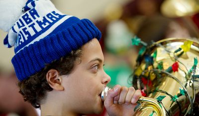 """Sporting his """"Tuba Christmas"""" hat, Bryce Gaskins, 11, of Alexandria, Va. rehearses with hundreds of other tuba players forTuba Christmas, a concert that originated in 1974 as a tribute to the late artist/teacher William J. Bell, who was born on Christmas Day in 1902.  (Barbara L. Salisbury/The Washington Times)"""