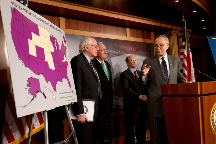 Sen. Charles E. Schumer (right), accompanied by (from left) Sens. Bernard Sanders, Tom Harkin and Chris Coons, gestures during a news conference on Capitol Hill in Washington on Thursday, Dec. 6, 2012, about the possibility of Americans abruptly losing their jobless benefits at the end of the year. (AP Photo/Jacquelyn Martin)