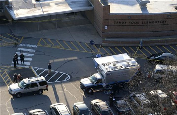 Officials are on the scene outside of Sandy Hook Elementary School in Newtown, Conn., where authorities say a gunman opened fire inside an elementary school in a shooting that left 27 people dead, including 20 children, Friday, Dec. 14, 2012. (AP Photo/Julio Cortez)