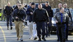 Law enforcement canvass the area following a shooting at the Sandy Hook Elementary School in Newtown, Conn., about 60 miles (96 kilometers) northeast of New York City, Friday, Dec. 14, 2012. An official with knowledge of Friday's shooting said 27 people were dead, including 18 children.  (AP Photo/Jessica Hill)
