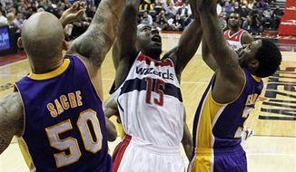 Washington Wizards guard Jordan Crawford (15) shoots between Los Angeles Lakers Robert Sacre (50) and forward Devin Ebanks (3) in the first half of an NBA basketball game Friday, Dec. 14, 2012 in Washington. The Lakers won 102-96. (AP Photo/Alex Brandon)