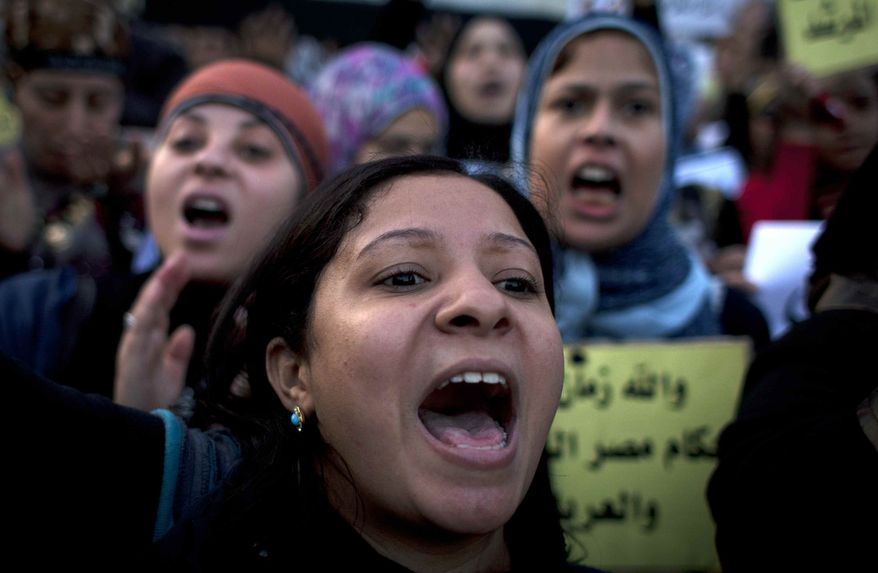 Women protesters opposing Egyptian President Mohammed Morsi chant slogans during a demonstration that started in front of el-Nour mosque, background, in Cairo, Egypt, Tuesday, Dec. 11, 2012. (AP Photo/Nasser Nasser)