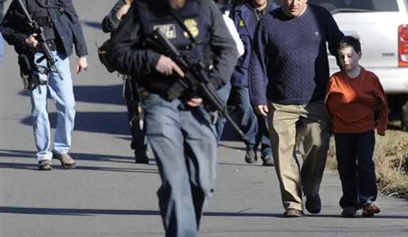 Parents leave a staging area after being reunited with their children following a shooting at the Sandy Hook Elementary School in Newtown, Conn., about 60 miles (96 kilometers) northeast of New York City, on Dec. 14, 2012. It was the worst school shooting in the country's history. (Associated Press)