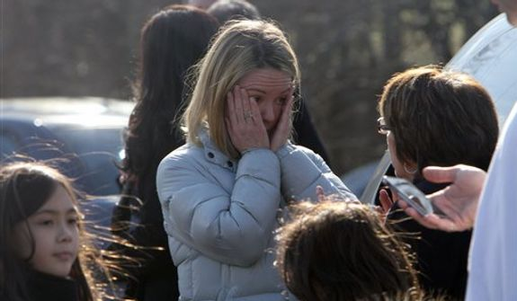 A woman weeps as she arrives to pick up her children at the Sandy Hook Elementary School, Friday, Dec. 14, 2012 in Newtown, Conn. A man opened fire inside the Connecticut elementary school where his mother worked Friday, killing 26 people, including 18 children, and forcing students to cower in classrooms and then flee with the help of teachers and police. (AP Photo/The Journal News, Frank Becerra Jr.) MANDATORY CREDIT, NYC OUT, NO SALES, TV OUT, NEWSDAY OUT; MAGS OUT