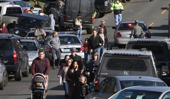 Parents walk away from the Sandy Hook School with their children following a shooting at the school Friday, Dec. 14, 2012 in Newtown, Conn. A man opened fire inside the Connecticut elementary school where his mother worked Friday, killing 26 people, including 18 children, and forcing students to cower in classrooms and then flee with the help of teachers and police. (AP Photo/The Journal News, Frank Becerra Jr.) MANDATORY CREDIT, NYC OUT, NO SALES, ONLINE OUT, TV OUT, NEWSDAY OUT; MAGS OUT