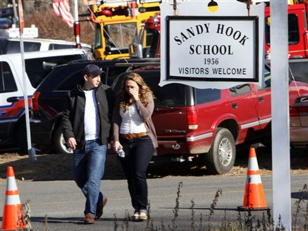Parents walk away from the Sandy Hook Elementary School in Newtown, Conn., on Friday, Dec. 14, 2012, after a gunman killed 20 schoolchildren and 6 adults there. (AP Photo/The Journal News, Frank Becerra Jr.)