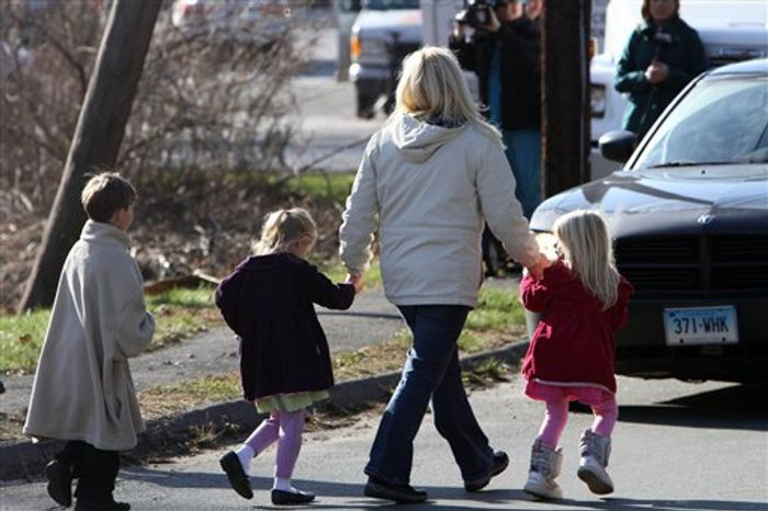 ** FILE ** Parents walk away from the Sandy Hook Elementary School with their children following a mass shooting at the school on Friday, Dec. 14, 2012, in Newtown, Conn. Twenty schoolchildren and six adults were killed. (AP Photo/The Journal News, Frank Becerra Jr.)