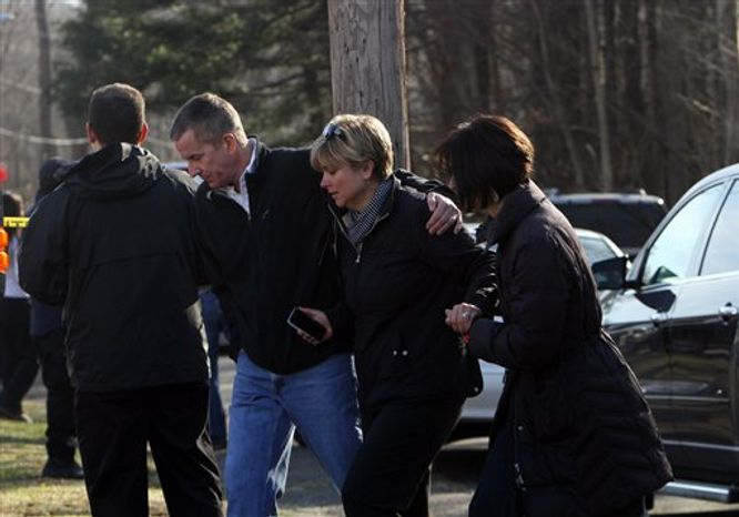 Teachers walk away from the Sandy Hook School following a shooting  at the school, Friday, Dec. 14, 2012 in Newtown, Conn. A man opened fire inside the Connecticut elementary school where his mother worked Friday, killing 26 people, including 18 children, and forcing students to cower in classrooms and then flee with the help of teachers and po