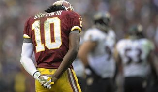 Washington Redskins quarterback Robert Griffin III stands during a timeout in the second half of an NFL football game against the Baltimore Ravens in Landover, Md., Sunday, Dec. 9, 2012. (AP Photo/Nick Wass)