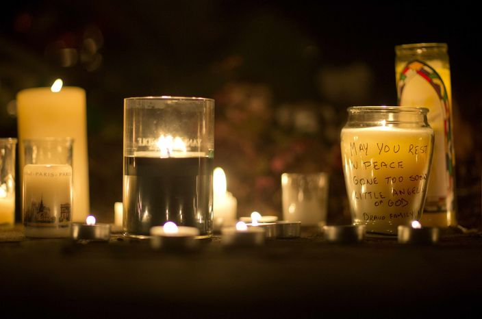 A message is seen on a candle outside the St. Rose of Lima Roman Catholic Church, Saturday, Dec. 15, 2012, in Newtown, Conn. A man killed his mother at their home and then opened fire Friday inside the Sandy Hook Elementary school, massacring 26 people, including 20 children, as youngsters cowered in fear to the sound of gunshots reverberating through the building and