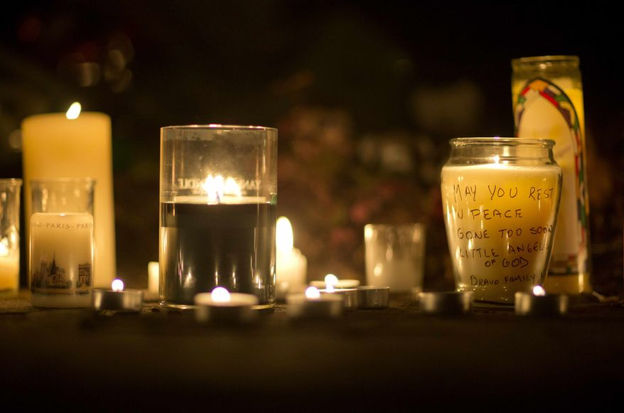 A message is seen on a candle outside the St. Rose of Lima Roman Catholic Church, Saturday, Dec. 15, 2012, in Newtown, Conn. A man killed his mother at their home and then opened fire Friday inside the Sandy Hook Elementary school, massacring 26 people, including 20 children, as youngsters cowered in fear to the sound of gunshots reverberating through the building and screams echoing over the intercom. (AP Photo/David Goldman)