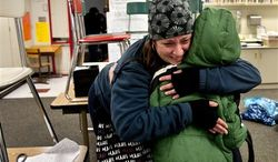 After watching TV news reports of the school shooting in Connecticut, Alicia Combo tightly hugs her son Morgan Askins at the close of school, Dec. 14, 2012, at Garfield Elementary in Spokane, Wash. (AP Photo/Spokesman Review, Dan Pelle)