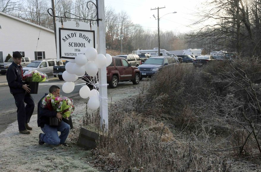 A couple of volunteer firefighters place flowers at a makeshift memorial at a sign for the Sandy Hook Elementary school, Saturday, Dec. 15, 2012, in Sandy Hook village of Newtown, Conn. (AP Photo/Mary Altaffer)