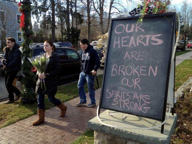 Jessica Henderson, 19, walks past a sign with a bouquet of flowers to lay at a memorial at the Sandy Hook School in Newtown, Conn., on Saturday, Dec. 15, 2012. The massacre of 26 children and adults at Sandy Hook Elementary school elicited horror and soul-searching around the world even as it raised more basic questions about why the gunman, 20-year-old Adam Lanza, would have been driven to such a crime and how he chose his victims. (AP Photo/Allen Breed)