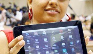 An Indian student shows the inexpensive Aakash 2 computer she received during its launch in New Delhi. The $25 basic touchscreen tablet aimed for students can be used for functions like word processing, Web browsing and video conferencing. The Indian government intends to deliver 10 million tablets to students across India. (Associated Press)