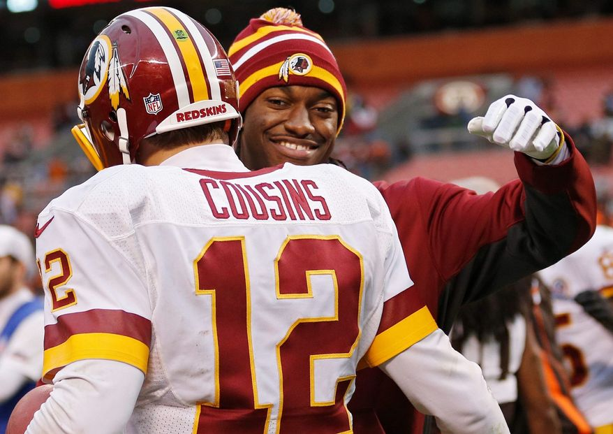 Injured Washington Redskins quarterback Robert Griffin III, right, hugs Kirk Cousins (12) after a 38-21 win over the Cleveland Browns in an NFL football game in Cleveland, Sunday, Dec. 16, 2012. Cousins passed for 329 yards and two touchdowns filling in for Griffin. (AP Photo/Rick Osentoski)