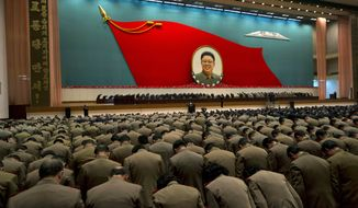 "** FILE ** North Korean military officers bow at an image of the late North Korean leader Kim Jong-il during a national meeting of top party and military officials on the eve of the first anniversary of Kim's death in Pyongyang, North Korea, on Sunday, Dec. 16, 2012. The large characters on the vertical banner at left translate as ""Hurrah to the Workers' Party of Korea."" (AP Photo/Ng Han Guan)"