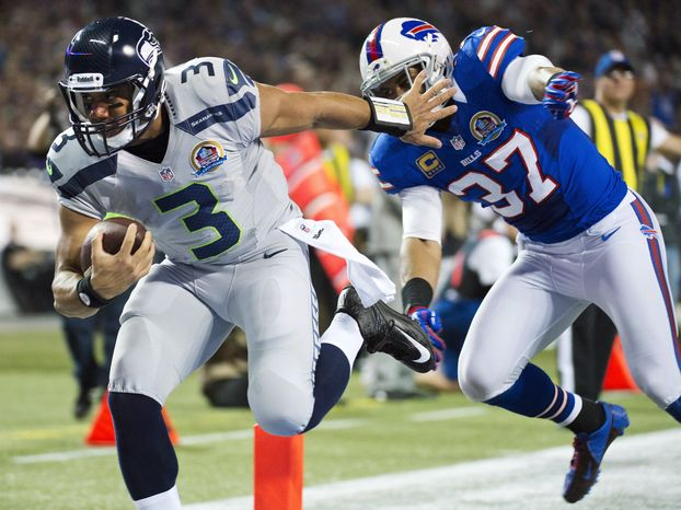 Seattle Seahawks quarterback Russell Wilson (3) runs the ball into the end zone for a touchdown past Buffalo Bills' George Wilson (37) during the first half of an NFL football game, Sunday, Dec. 16, 2012, in Toronto. (AP Photo/The Canadian Press, Nathan Denette)