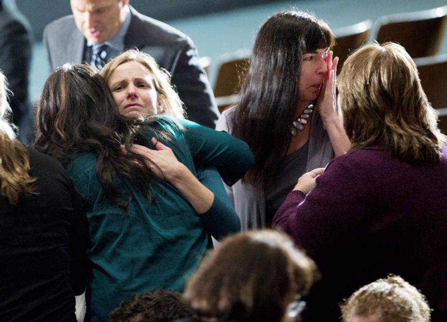 Residents greet each other before an interfaith vigil for the victims of the Sandy Hook Elementary School shooting on Sunday, Dec. 16, 2012 at Newtown High School in Newtown, Conn.  A gunman walked into Sandy Hook Elementary School Friday and opened fire, killing 26 people, including 20 children.  (AP Photo/ Evan Vucci)