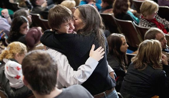 Residents greet each other before an interfaith vigil for the victims of the Sandy Hook Elementary School shooting on Sunday, Dec. 16, 2012 at Newtown High School in Newtown, Conn.  (AP Photo/ Evan Vucci)