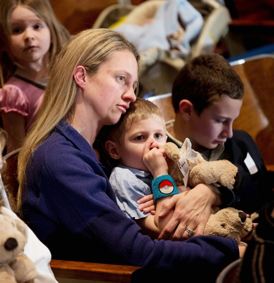 Residents wait for the start of an interfaith vigil for the victims of the Sandy Hook Elementary School shooting on Sunday, Dec. 16, 2012 at Newtown High School in Newtown, Conn.  (AP Photo/Evan Vucci)