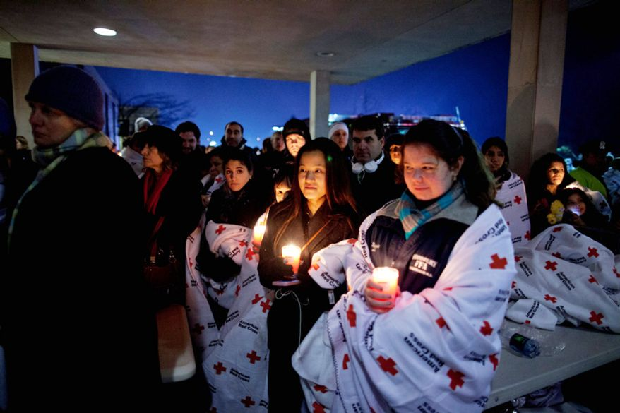 Residents hold a candlelight vigil outside Newtown High School after President Barack Obama delivered remarks at an interfaith vigil for the victims of the Sandy Hook Elementary School shooting on Sunday, Dec. 16, 2012, at Newtown High School in Newtown, Conn.  (AP Photo/ Evan Vucci)