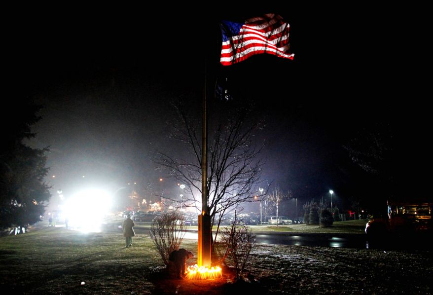A young boy places a candle with others at the base of a flagpole outside Newtown High School before an interfaith vigil with President Barack Obama, Sunday, Dec. 16, 2012, in Newtown, Conn.   (AP Photo/Jason DeCrow)