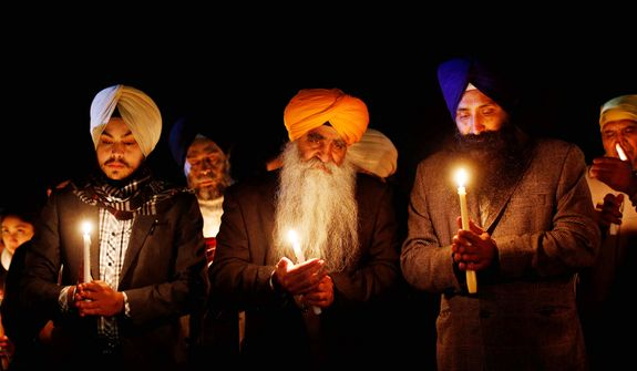 The 500,000 Sikhs who live in America are often misidentified as terrorists by fellow citizens who know little or nothing about the traditional faith, a new study revealed. In this photo, members of the Sikh community hold a candlelight vigil outside Newtown High School before an interfaith vigil with President Barack Obama, Sunday, Dec. 16, 2012, in Newtown, Conn. (AP Photo/Jason DeCrow)