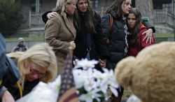 Women embrace at the site of a makeshift memorial for school shooting victims at the village of Sandy Hook in Newtown, Conn., on Sunday, Dec. 16, 2012. A gunman opened fire at Sandy Hook Elementary School in the town, killing 26 people, including 20 children, before killing himself on Friday. (AP Photo/Charles Krupa)