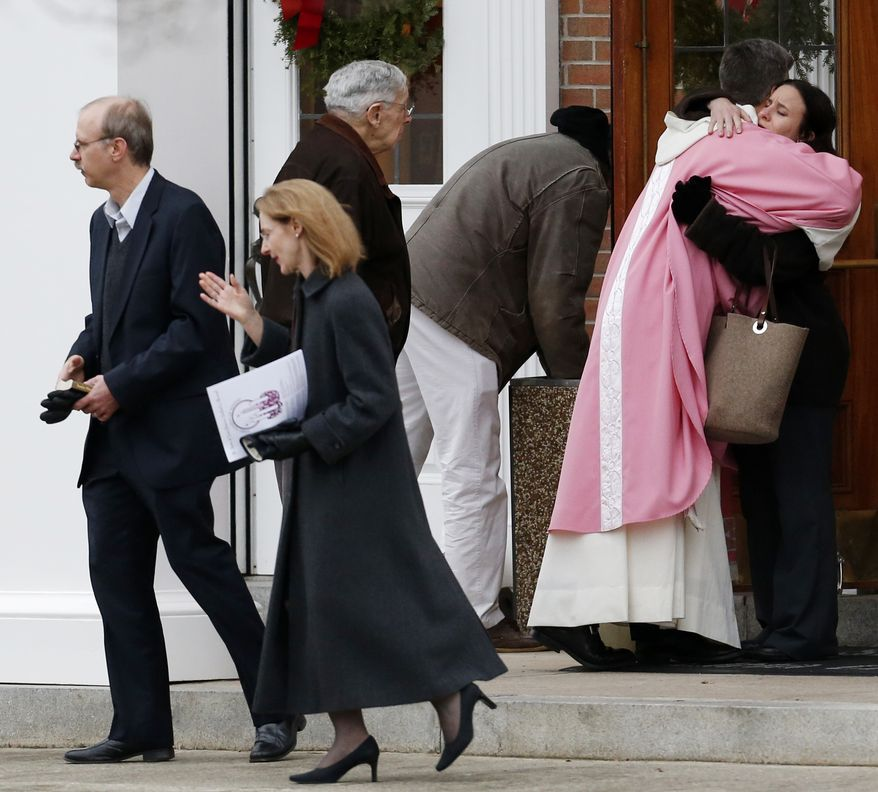 A priest embraces a woman outside St. Rose of Lima Roman Catholic Church between Masses on Sunday, Dec. 16, 2012, in Newtown, Conn. (AP Photo/Julio Cortez)