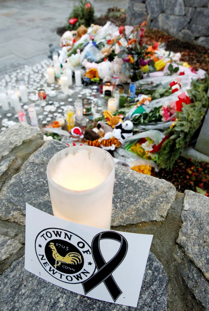 A note rests next to a candle near a makeshift memorial outside of St. Rose of Lima Roman Catholic Church following a Sunday Mass, Sunday, Dec. 16, 2012, in Newtown, Conn.  (AP Photo/Julio Cortez)