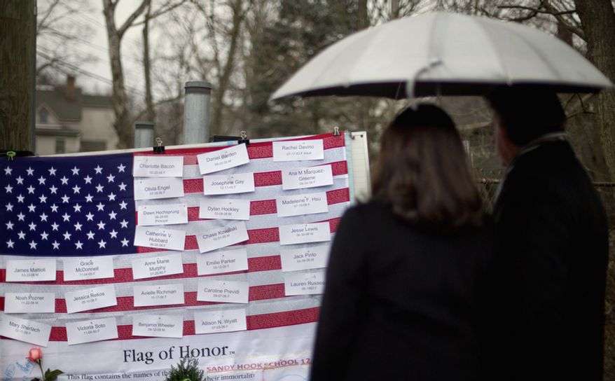 Mourners looks at the names on a U.S. flag of the Sandy Hook Elementary School shooting victims at a sidewalk memorial, Sunday, Dec. 16, 2012, in Newtown, Conn. (AP Photo/David Goldman)