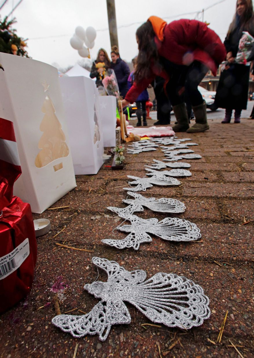 A woman lays flowers at the site of a makeshift memorial for school shooting victims at the village of Sandy Hook in Newtown, Conn. (AP Photo/Charles Krupa)