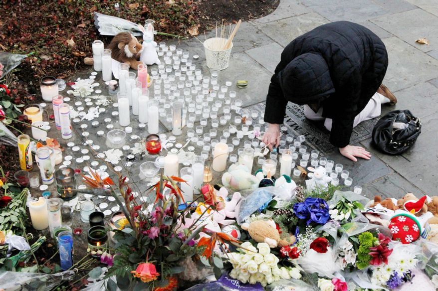 A woman pays respects at a memorial outside of St. Rose of Lima Roman Catholic Church, Sunday, Dec. 16, 2012, in Newtown, Conn.  (AP Photo/Julio Cortez)