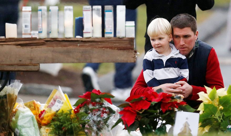 A man holds a child while paying respects to shooting victims at a makeshift memorial outside of St. Rose of Lima Roman Catholic Church, Sunday, Dec. 16, 2012, in Newtown, Conn. (AP Photo/Julio Cortez)