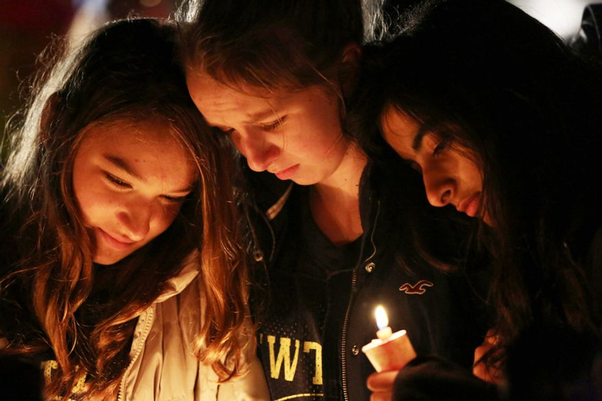Kate Suba, left, Jaden Albrecht, center, and Simran Chand pay their respects at one of the makeshift memorials in honor of the victims of the Sandy Hook Elementary School shooting, Sunday, Dec. 16, 2012, in Newtown, Conn.  (AP Photo/Mary Altaffer)