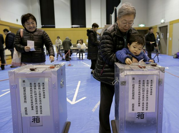 A boy slips his grandmother's vote into a ballot box at a polling station in Tokyo on Sunday, Dec. 16, 2012. (AP Photo/Itsuo Inouye)