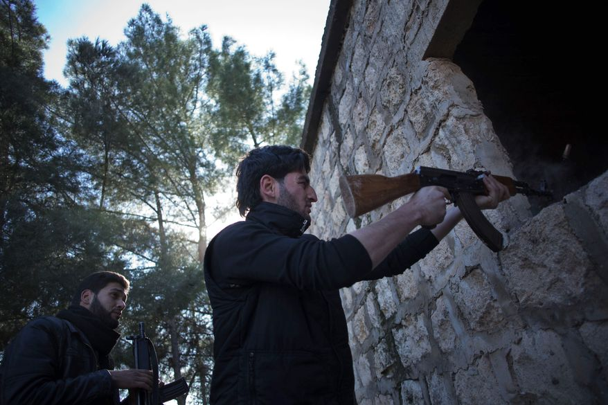 A Free Syrian Army fighter fires his machine gun toward Syrian army positions during an assault on a military base in Tal Sheen, Syria, on Saturday, Dec. 15, 2012. (AP Photo/Manu Brabo)