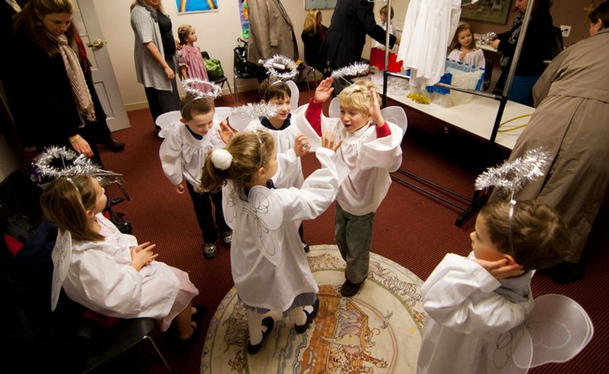Children part of the Christ Church Sunday school and youth group dress up as angels and rehearse their song before their Christmas Pageant in Alexandria, Va., on Sunday, December 16, 2012. (Craig Bisacre/The Washington Times)