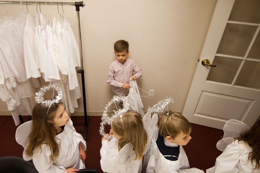Children part of the Christ Church Sunday school and youth group get dressed up as angels before their Christmas Pageant in Alexandria, Va., on Sunday, December 16, 2012.  (Craig Bisacre/The Washington Times)