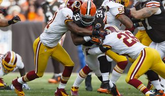 Cleveland Browns running back Trent Richardson (33) runs the ball as Washington Redskins cornerback Josh Wilson (26) and free safety Madieu Williams (41) tackle him during an NFL football game in Cleveland, Sunday, Dec. 16, 2012. (AP Photo/Rick Osentoski)